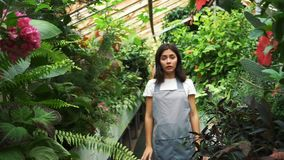 The girl in the greenhouse in the apron, itching from pollen plants. Allergic to flowers.  stock footage