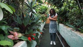 The girl in the greenhouse in the apron, itching from pollen plants. Allergic to flowers.  stock video footage