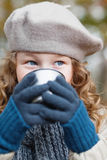Girl in grey beret drinking from flask cup. Outdoor portrait of a girl in winter cloths drinking from flask cup Stock Photo