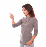 Girl in grey blouse pointing to her right Stock Photography
