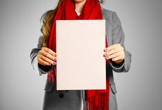 A girl in grey coat and red scarf keeps a beige clean blank shee. T of A4.  on grey background Royalty Free Stock Photos