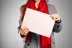 A girl in grey coat and red scarf keeps a beige clean blank shee. T of A4. Isolated on grey background Royalty Free Stock Photo