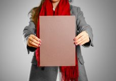 A girl in grey coat and red scarf keeps a brown clean blank shee. T of A4.  on grey background Royalty Free Stock Photography