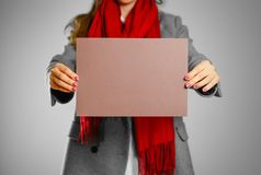 A girl in grey coat and red scarf keeps a brown clean blank shee. T of A4. Isolated on grey background Stock Photos