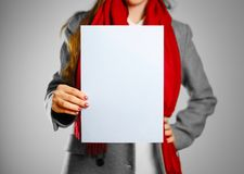 A girl in grey coat and red scarf keeps a light blue clean blank. Sheet of A4.  on grey background Stock Image