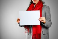 A girl in grey coat and red scarf keeps a light blue clean blank. Sheet of A4. Isolated on grey background Royalty Free Stock Image