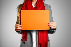 A girl in grey coat and red scarf keeps a orange clean blank she. Et of A4.  on grey background Royalty Free Stock Photos