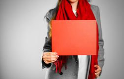 A girl in grey coat and red scarf keeps a red clean blank sheet. Of A4.  on grey background Royalty Free Stock Image