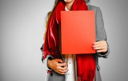 A girl in grey coat and red scarf keeps a red clean blank sheet. Of A4. Isolated on grey background Stock Photo