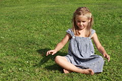 Girl in grey dress concentrating. Basrefoot girl in a grey dress sitting on the grass and concentrating stock image