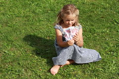 Girl in grey dress sitting with money. Basrefoot girl in a grey dress sitting on the grass watching lots of euros royalty free stock image