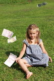 Girl in grey dress sitting watching flying money. Basrefoot girl in a grey dress sitting on the grass and watching lots of flying euros royalty free stock images