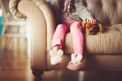 Girl in Grey Jacket and Pink Jeans Sitting in Grey Sofa Holding a Brown Short Coated Puppy Stock Images
