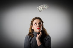 Girl in grey and one dollar. Royalty Free Stock Photos