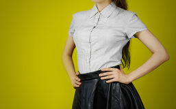 The girl in the grey shirt and leather skirt. Isolated on yellow. Background Stock Images