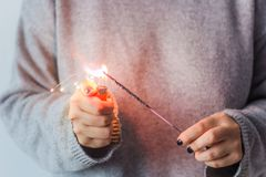 Woman  holding a sparkler. Girl in the grey sweater ignites the sparkler Royalty Free Stock Photos