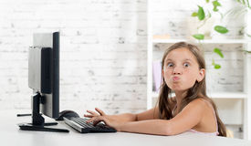 A girl grimaced front of a computer Stock Photo