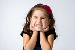 Girl Gritting Teeth. Adorable and expressive girl gritting her teeth and scrunching her face in a silly grin Royalty Free Stock Photos