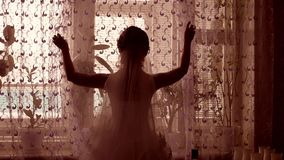 Girl groom opens the curtains in the room by the window silhouette Royalty Free Stock Photography