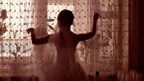 Girl groom opens the curtains in the room by the window silhouette Stock Photos