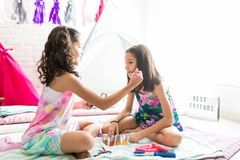 Girl Grooming Friend For Pajama Party At Home. Cute preteen girl grooming friend for pajama party at home stock photography
