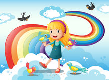 A girl and a group of birds in the sky near the rainbow Royalty Free Stock Image