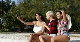 Girl Group Taking Selfie Photo On Cell Smart Phone Sitting Outdoors Under Palm Trees, Happy Smiling Woman Friends. Slow Motion 60 stock video