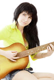 Girl with a guitar. Portrait of a young charming black-haired girl with a guitar Stock Photography