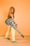 Girl with guitar. Red hair girl with  guitar standing over vivid background Royalty Free Stock Photography