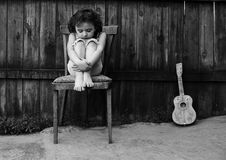 The girl with a guitar. The small sad girl sits on a chair near to a guitar Royalty Free Stock Image