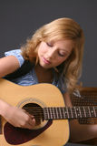 Girl with Guitar. Teenage girl wearing blue top against dark background playing guitar Royalty Free Stock Images