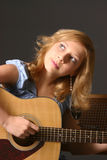 Girl with Guitar. Teenage girl wearing blue top against dark background playing guitar Royalty Free Stock Image