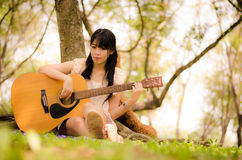Girl and the guitar. Asian girl playing guitar under a tree in the garden Stock Photo