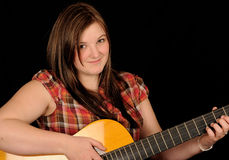 Girl with guitar. Girl wearing plaid shirt playing a guitar Royalty Free Stock Photo