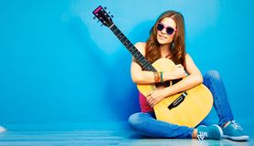 Girl with guitar against blue . hipster style portrait Stock Image