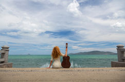 The girl with a guitar. Beautiful red-haired girl sitting on the beach with a guitar royalty free stock photo