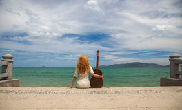 The girl with a guitar. Beautiful red-haired girl sitting on the beach with a guitar royalty free stock images