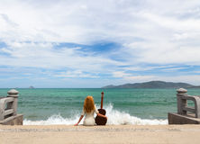 The girl with a guitar. Beautiful red-haired girl sitting on the beach with a guitar royalty free stock photos