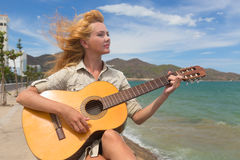 The girl with a guitar. Beautiful red-haired girl sitting on the beach with a guitar royalty free stock photography