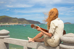 The girl with a guitar. Beautiful red-haired girl sitting on the beach with a guitar stock photo