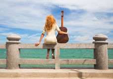 The girl with a guitar. Beautiful red-haired girl sitting on the beach with a guitar stock photos