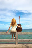 The girl with a guitar. Beautiful red-haired girl sitting on the beach with a guitar stock photography