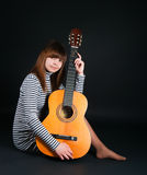 Girl with a guitar on a black background Stock Image