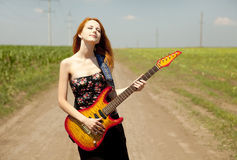 Girl with guitar at countryside. Royalty Free Stock Photo