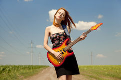 Girl with guitar at countryside. Royalty Free Stock Photos