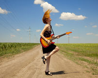 Girl with guitar at countryside. Stock Image