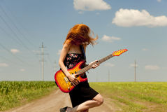 Girl with guitar at countryside. Stock Photography