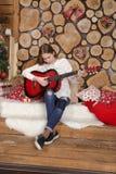 Girl with a guitar in a festive interior stock photos