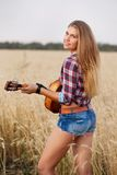 Girl with guitar in the field Royalty Free Stock Photography