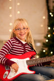 Girl with guitar in front of Christmas tree Stock Photography